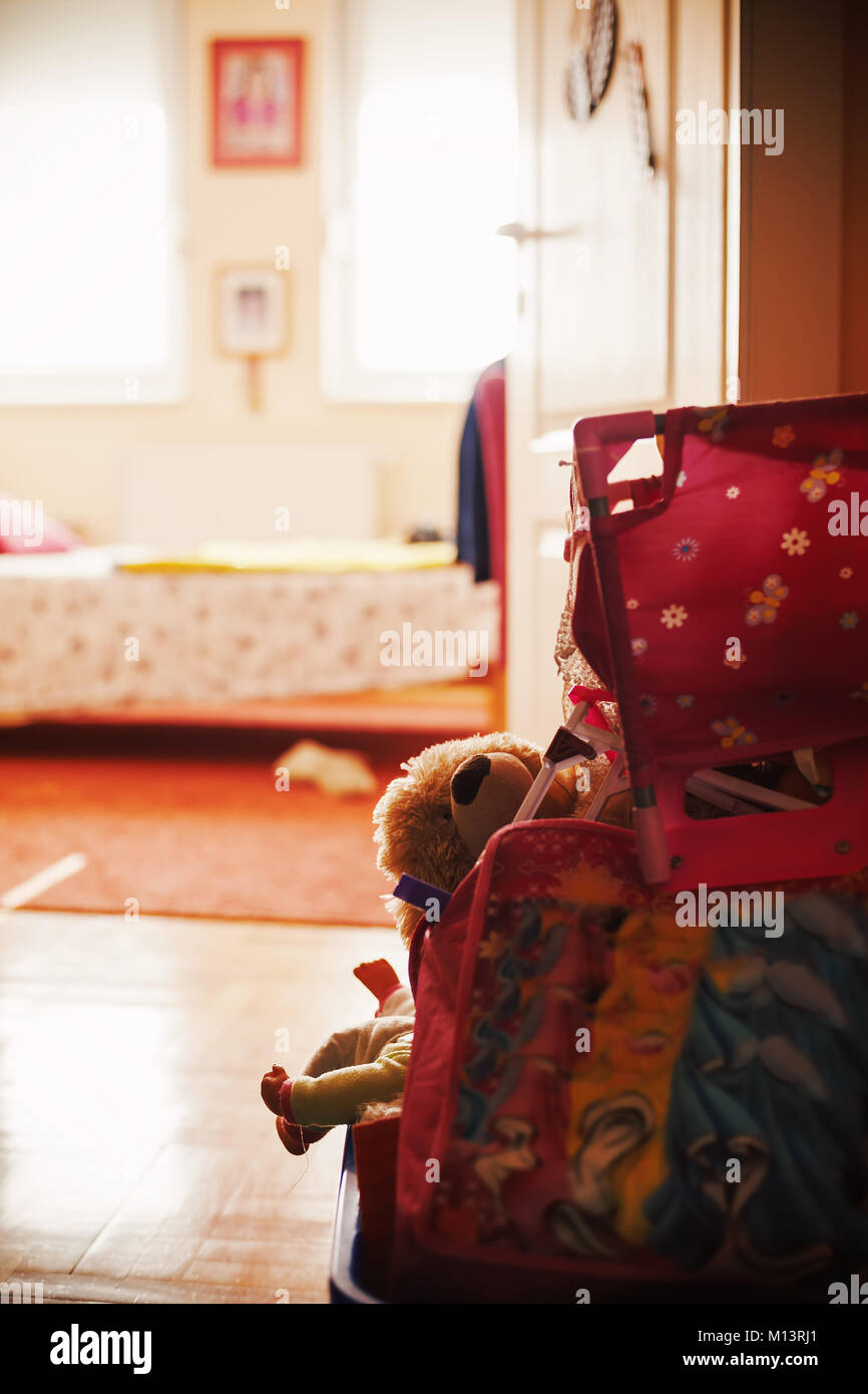 Closeup view on child's toys in basket in front of bedroom during day. Ordinary lifestyle concept. - Stock Image