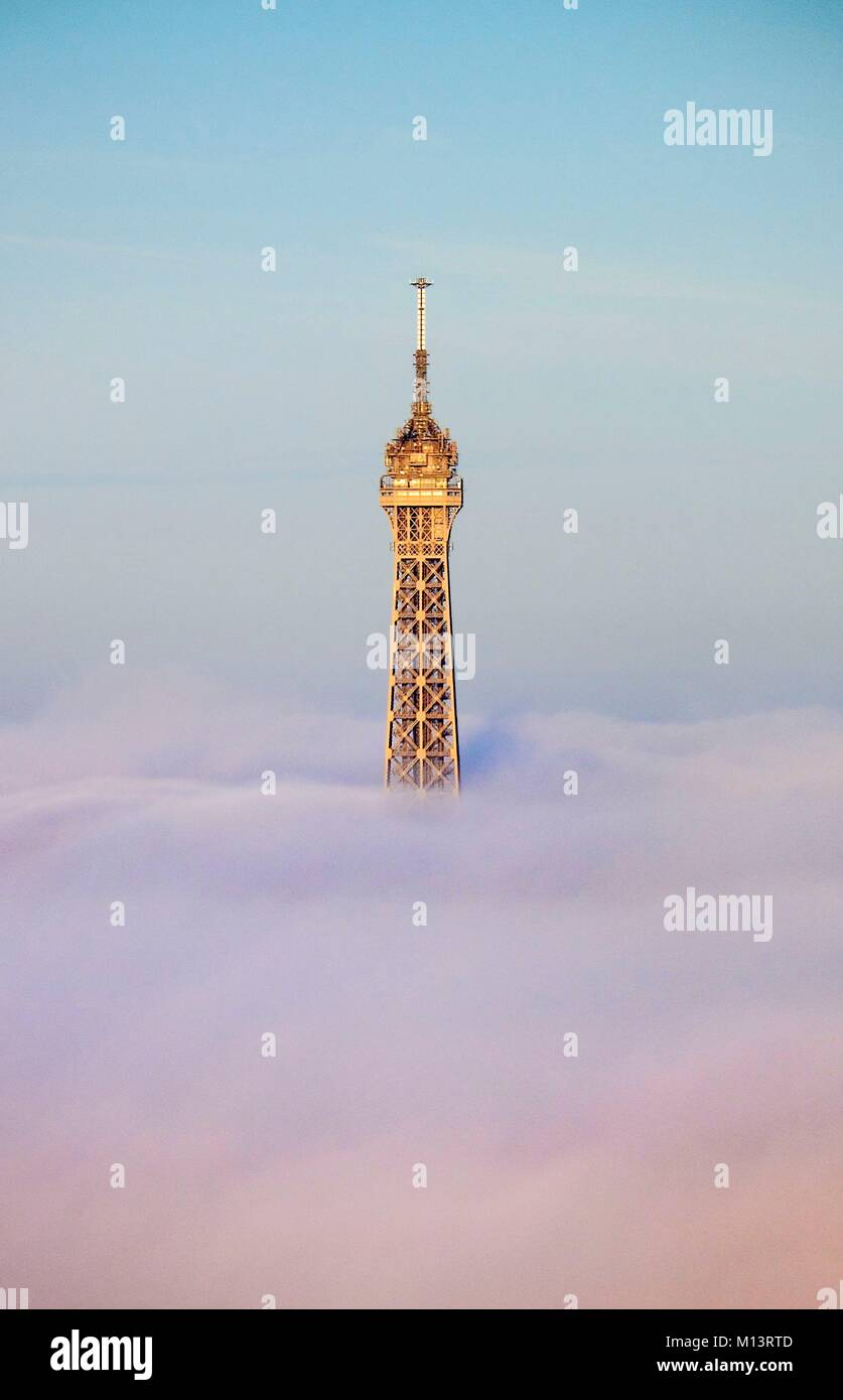 France, Paris, Paris, area listed as World Heritage by UNESCO, the Eiffel tower over the fog (aerial view) Stock Photo