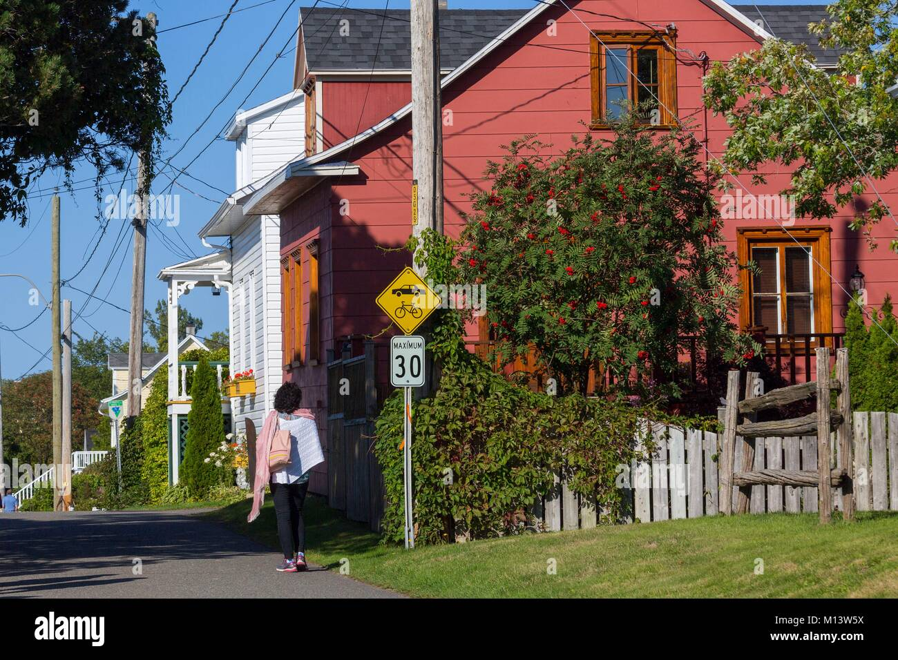 Canada, province of Quebec, Bas-Saint-Laurent region, the village of Kamouraska, the beautiful old houses, a passerby - Stock Image