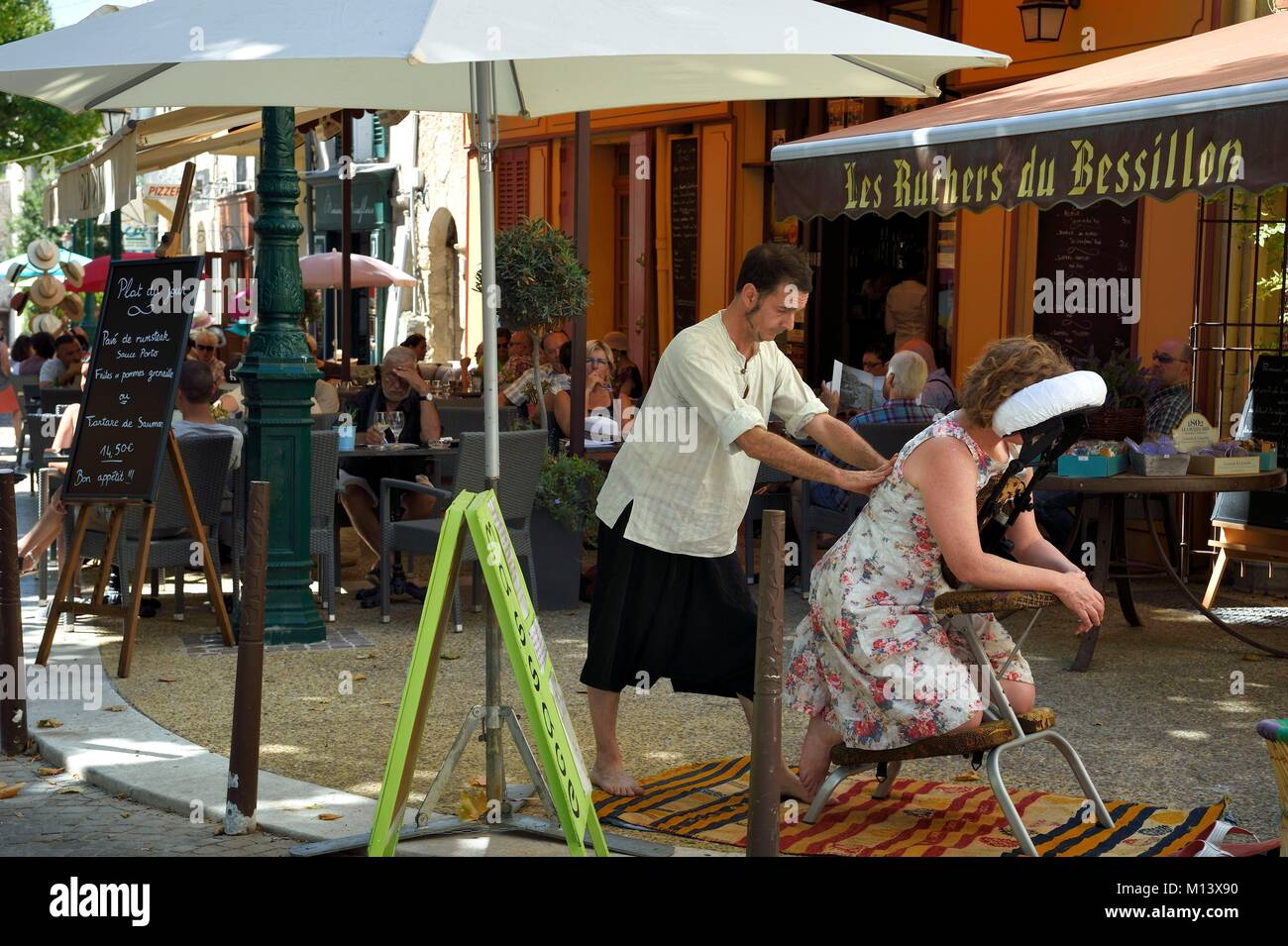 France, Var, Provence Verte, Cotignac, market day on the main square, massage in the street - Stock Image