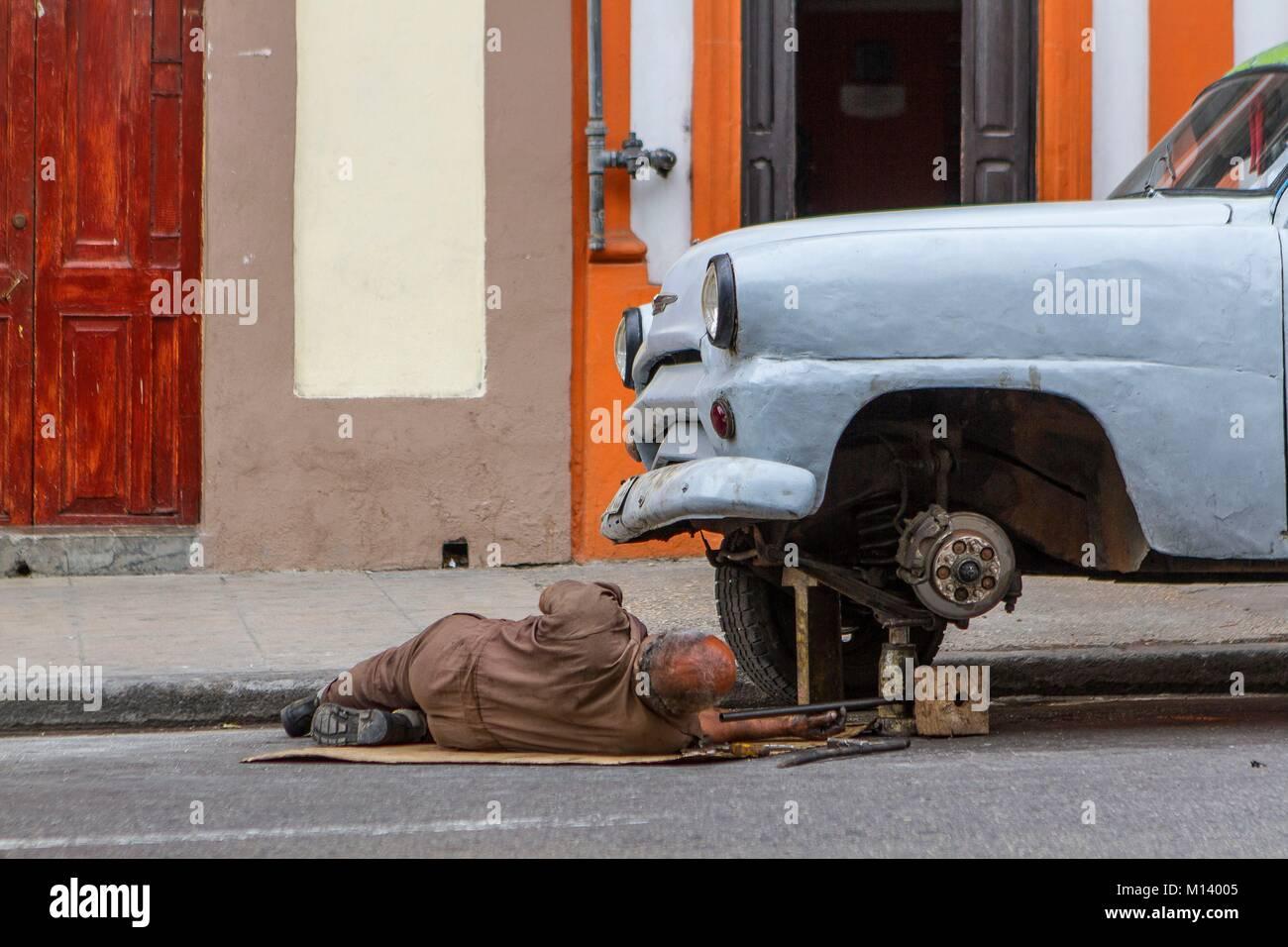 Cuba, province of Ciudad de la Habana, Havana, district of Centro Habana, man repairing an old american car Stock Photo