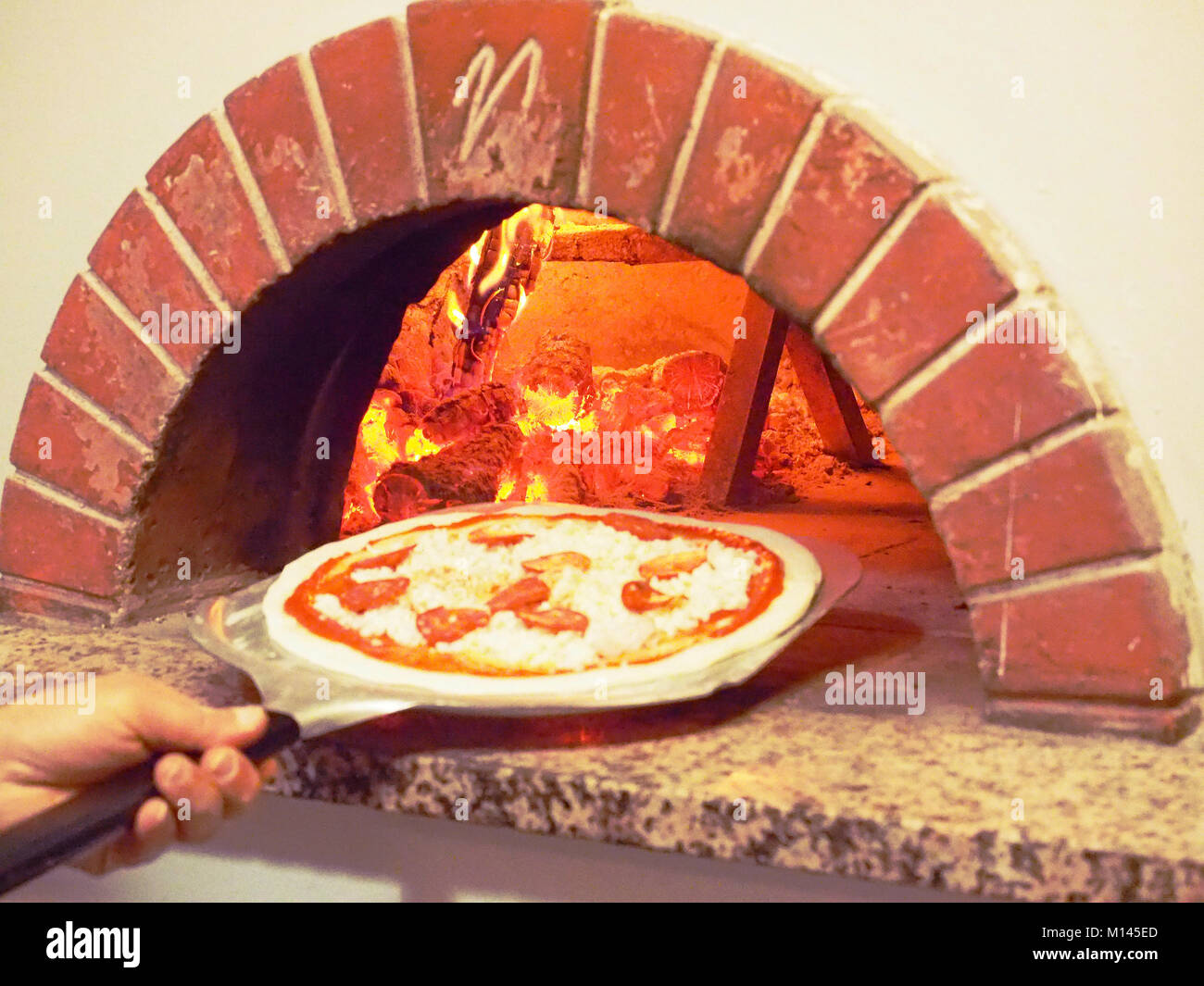 Europe,Italia,Pizzeria,Pizza in front of a wood oven - Stock Image