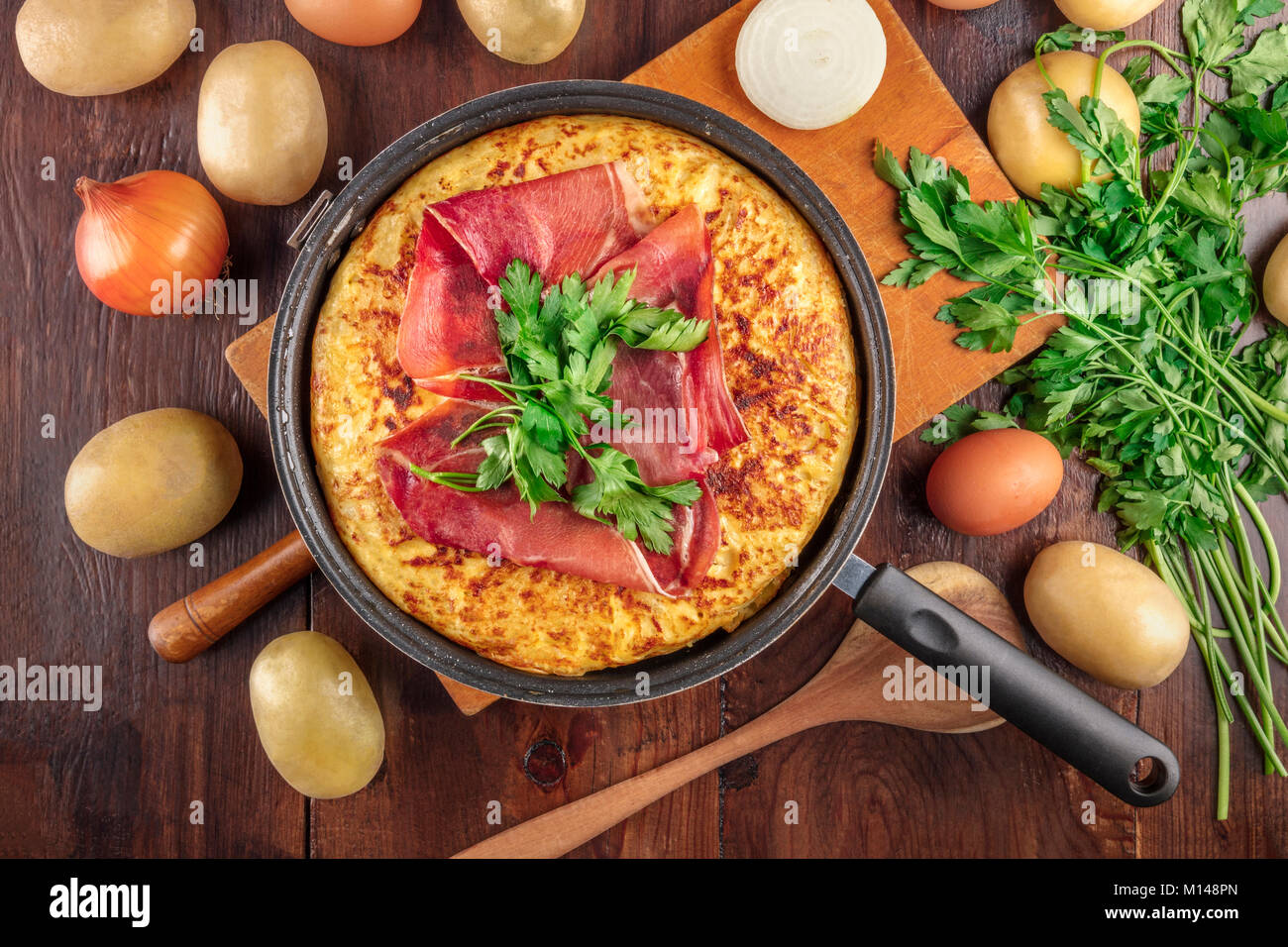 Spanish tortilla, shot from above with ingredients and copyspace - Stock Image
