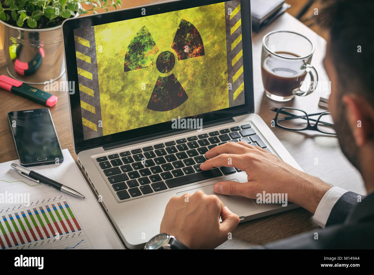 Man working in the office, radiation symbol on the laptop screen, - Stock Image