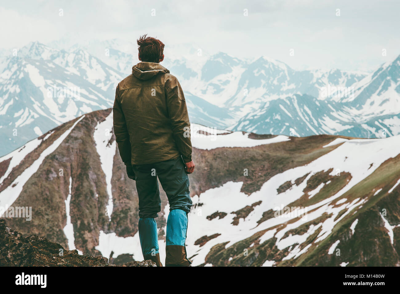 Climber Man reached mountain summit Travel Lifestyle concept traveler enjoying  landscape outdoor activity vacations - Stock Image