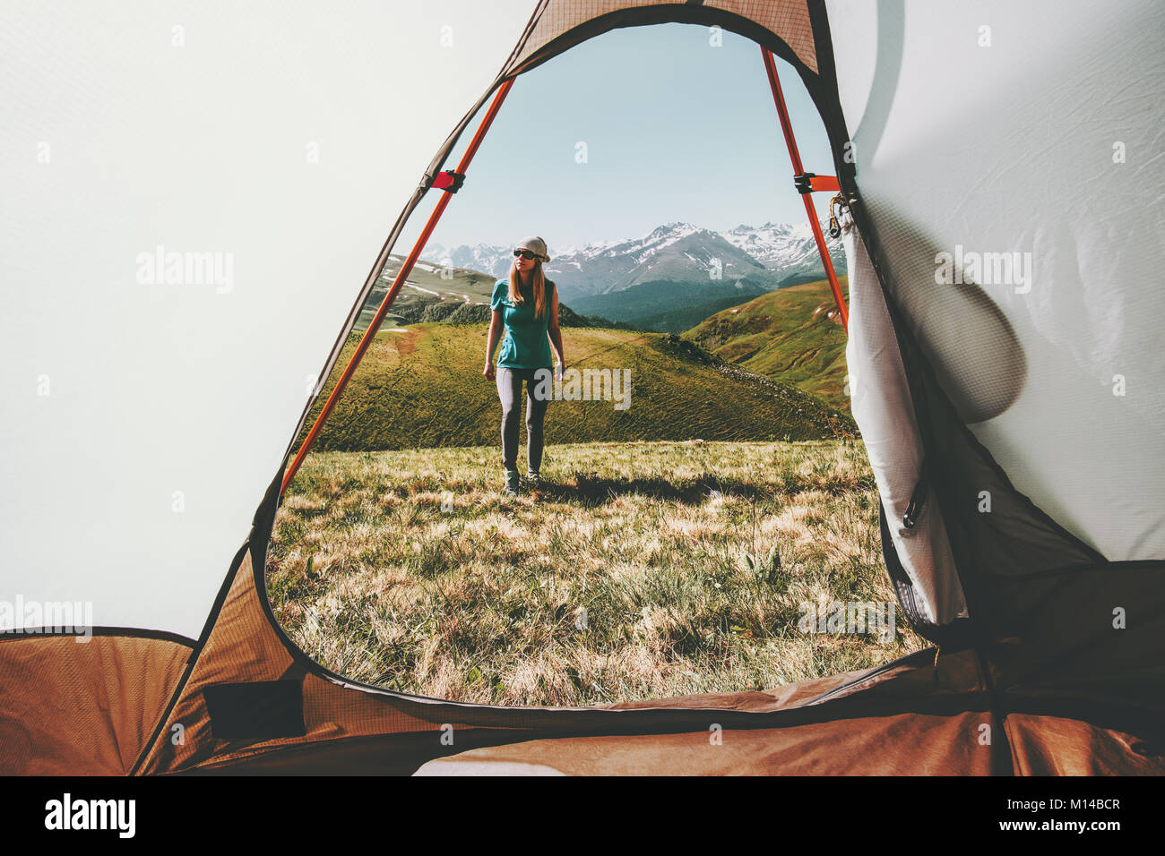 Woman traveler walking in mountains view from tent camping entrance outdoor Travel Lifestyle concept adventure summer - Stock Image