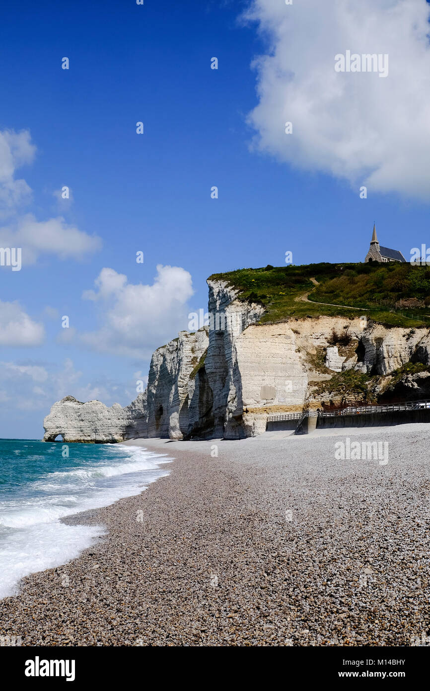 View of Chapelle Notre Dame de la Garde on the hilltop above the white chalk cliff and beach of the coast at Etretat, - Stock Image