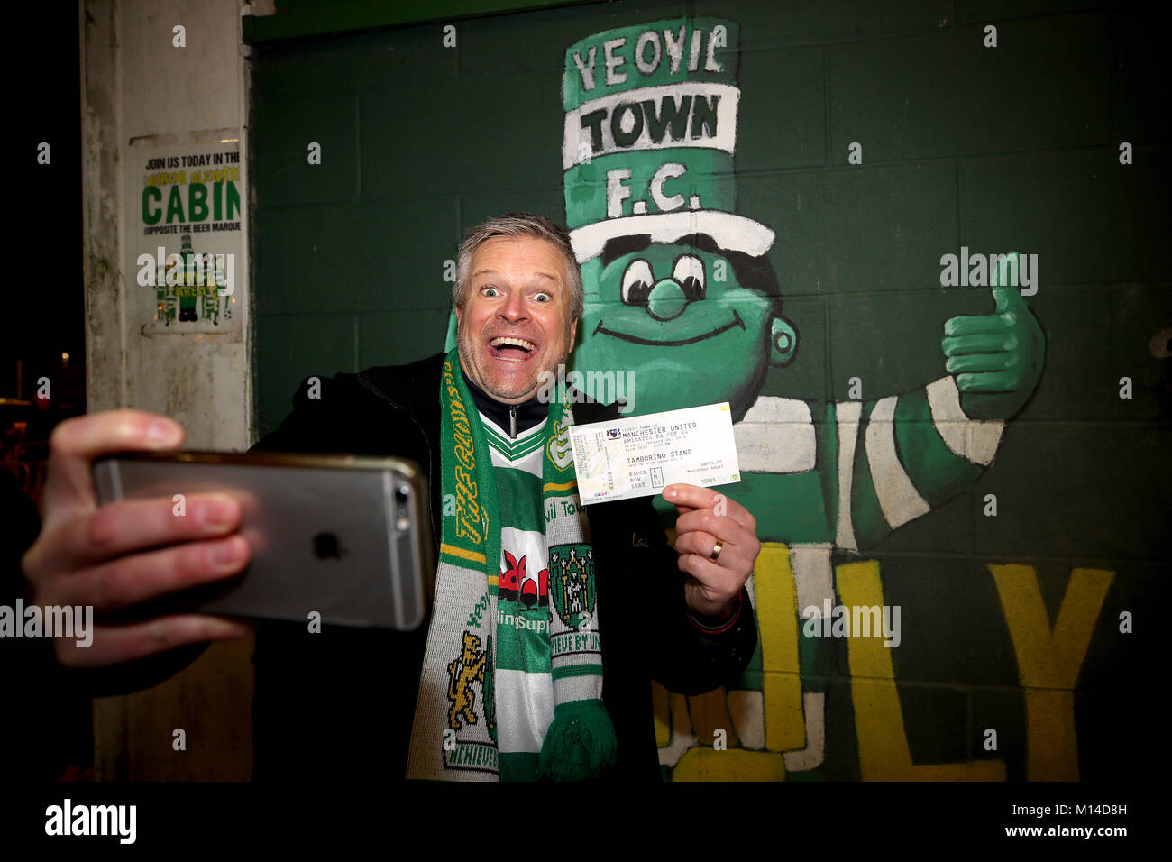 A Yeovil Town fan poses for a selfie with his ticket and the club mascot Jolly Green Giant in the background during - Stock Image