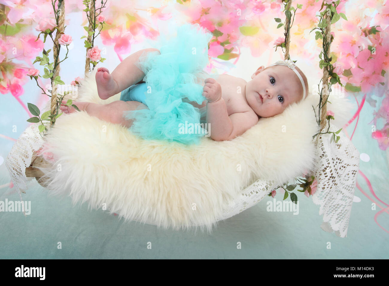 15 week old baby girl laying down relaxing on sensory bed - Stock Image