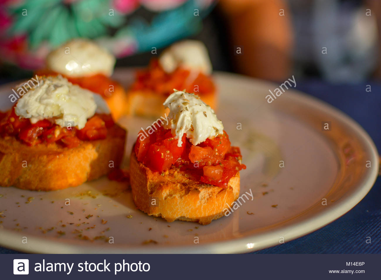 A tasty Italian appetizer of bruschetta on a plate in with tomatoes, basil, cheese and toasted bread - Stock Image