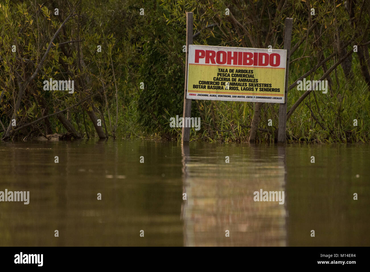 A sign by the Amazon river warning people that poaching, hunting,commercial fishing, and illegal activities will - Stock Image
