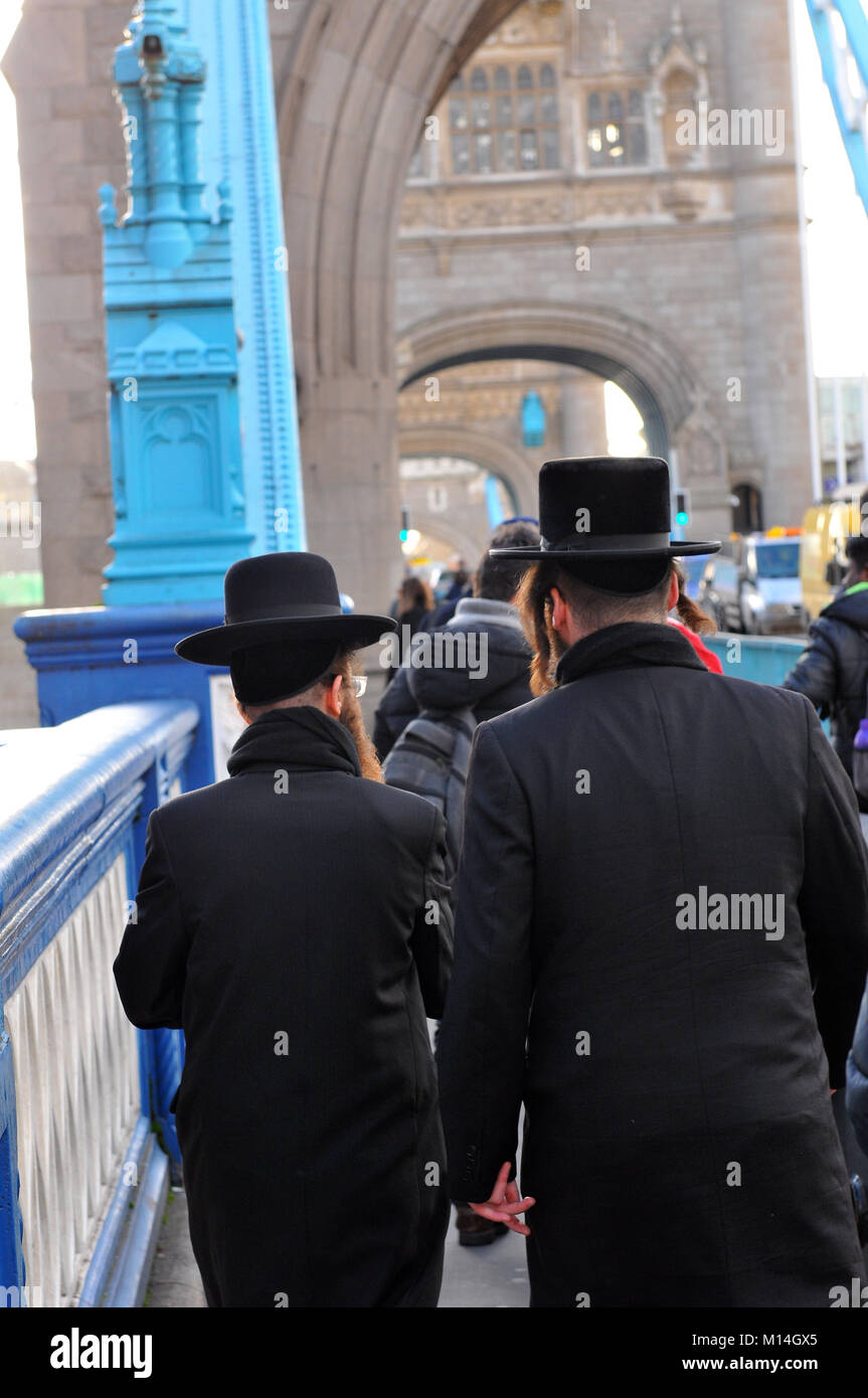 two orthodox jewish gentlemen walking across tower bridge in central London. hats and beards dressed in black the - Stock Image