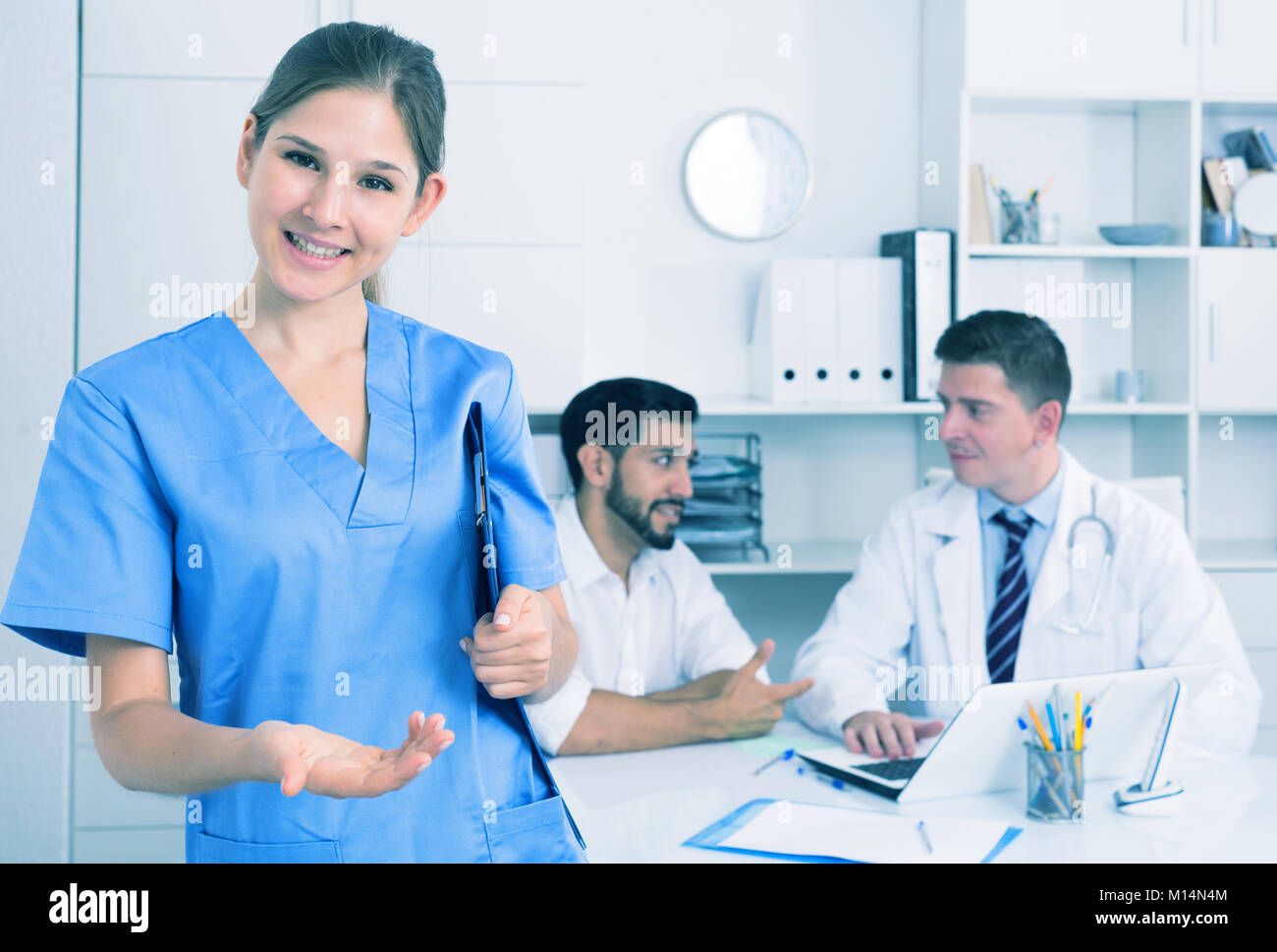 Portrait of young female doctor meeting patient in medical office - Stock Image