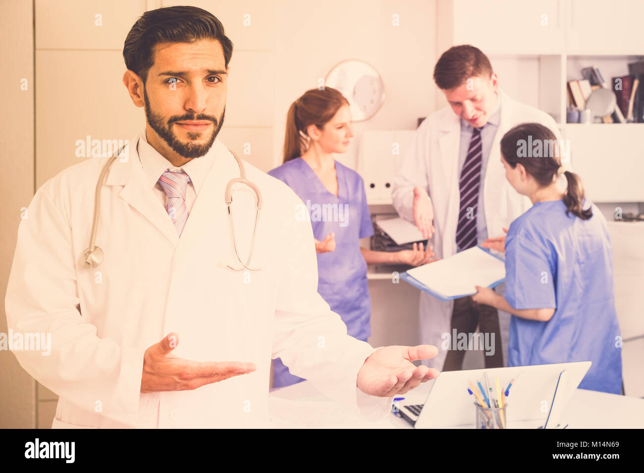 Bearded doctor making welcome gesture, politely inviting patient in medical office - Stock Image