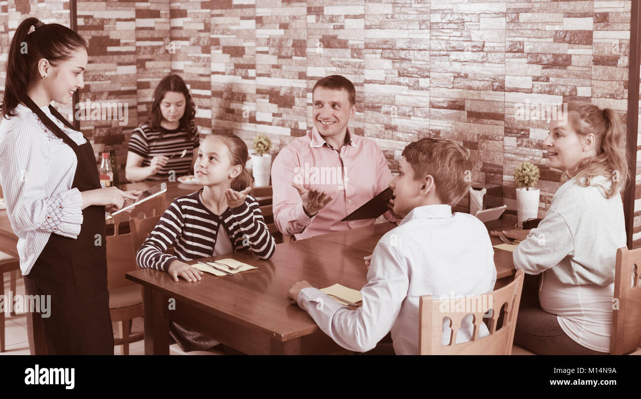 Adults with kids are giving order to cheerful waitress in comfy cafe. - Stock Image