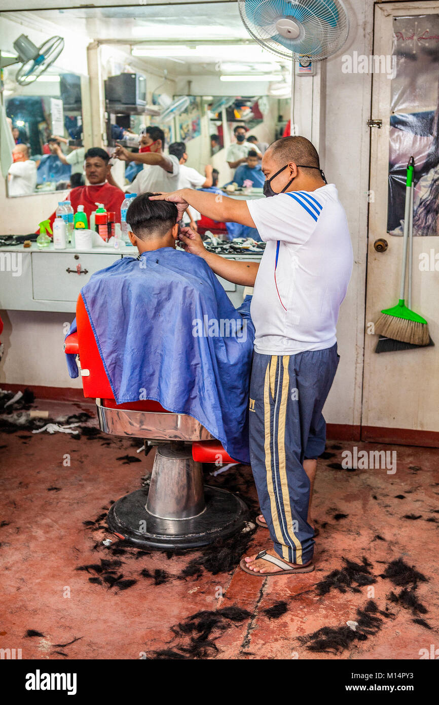 A Filipino barber cuts a high and tight fade hairstyle on a young man in Barretto, Luzon, Philippines. - Stock Image
