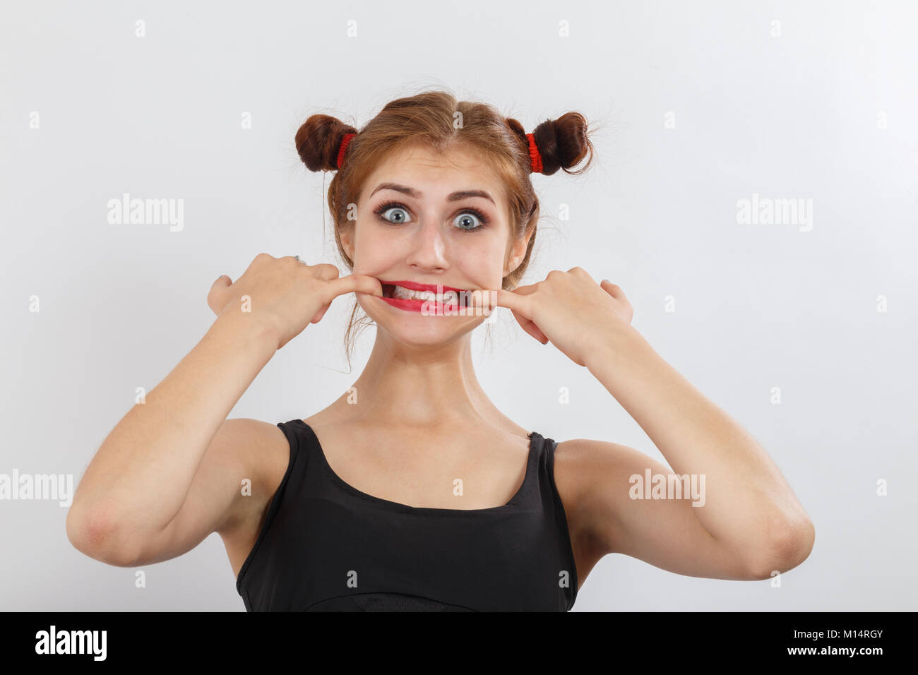 fun woman grimacing shows her teeth on white background - Stock Image