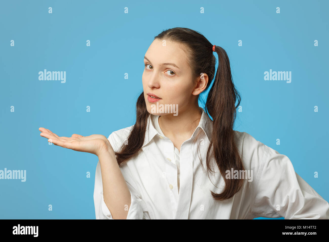 serious girl on blue background show open palm with place for product - Stock Image