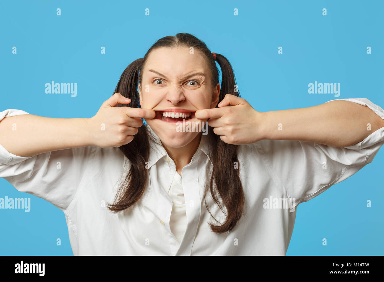 fun woman grimacing shows her teeth on blue background - Stock Image