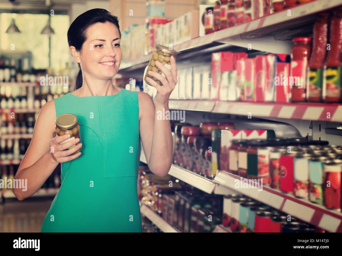 Female is holding jar of preserved olives in the shop. - Stock Image