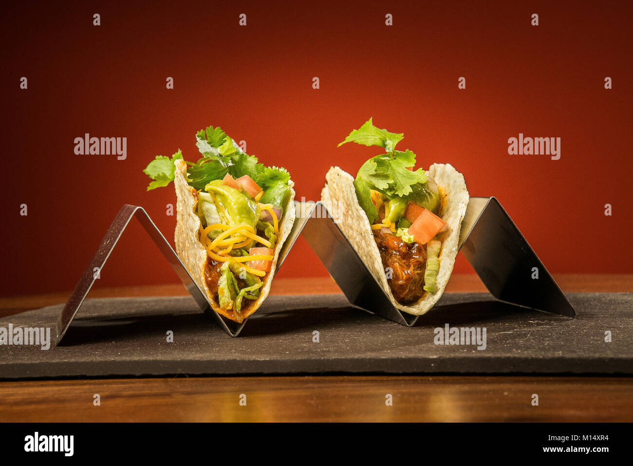 Pulled Pork Taco on a stainless steel stand with a red background on a stone surface and wood table. Photography - Stock Image