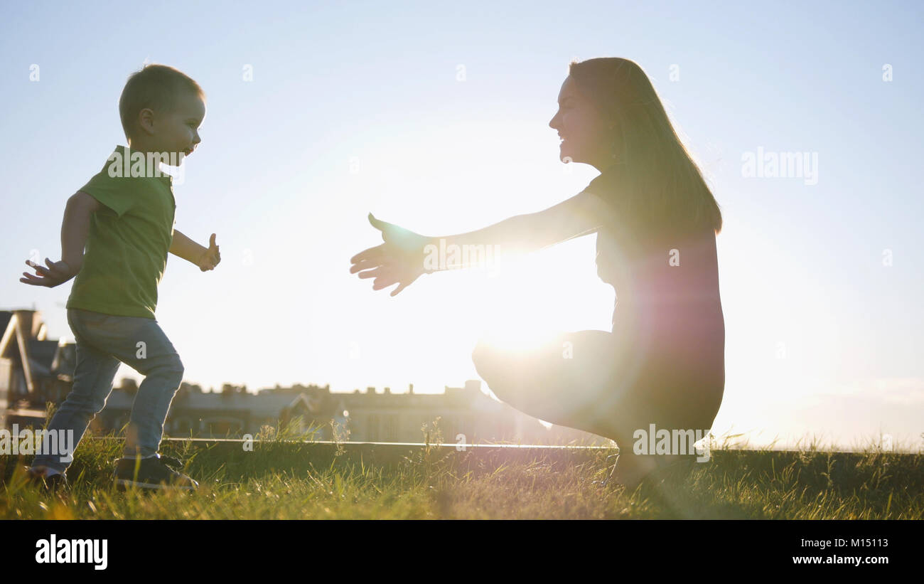 Mother plays with son in summer sunset park - child running to mommy - Stock Image