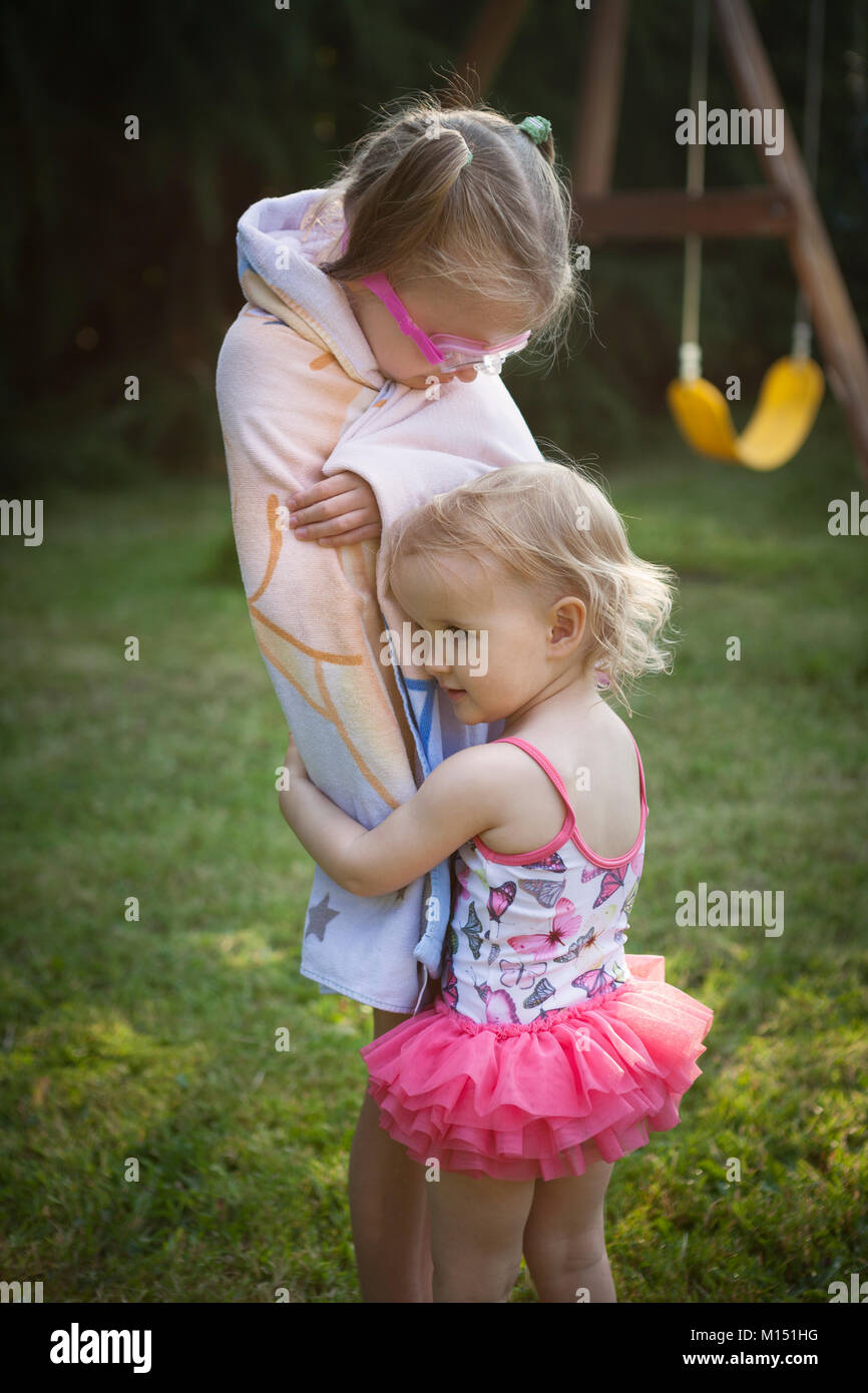 Child wrapped in towel being hugged by smaller child in swimming costume, outdoors in a back yard on a summer day - Stock Image