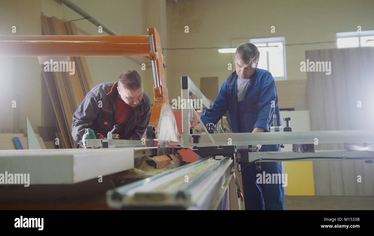 Men - carpenters are cutting wood on electric saw at furniture factory - Stock Image