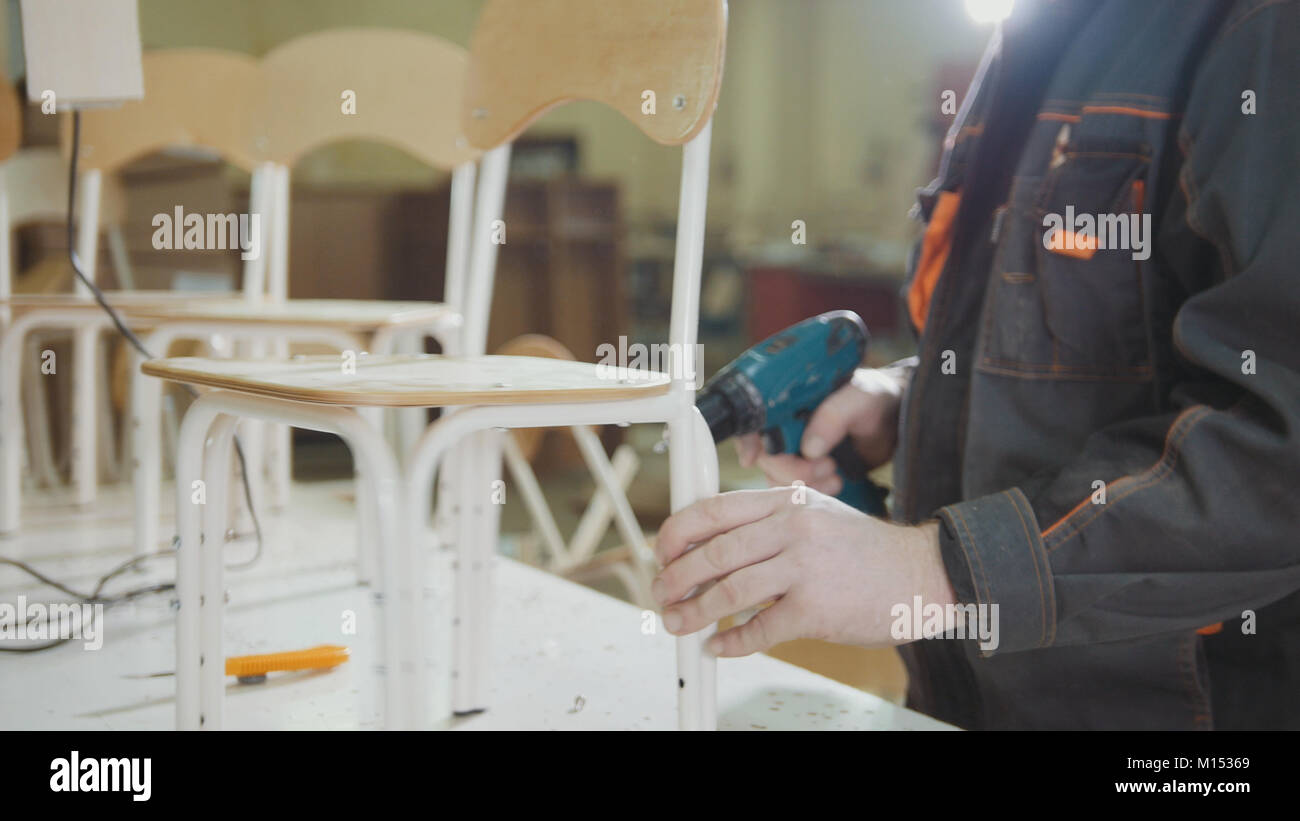 Worker carpenter is screwing chair for choldren on a furniture factory - Stock Image