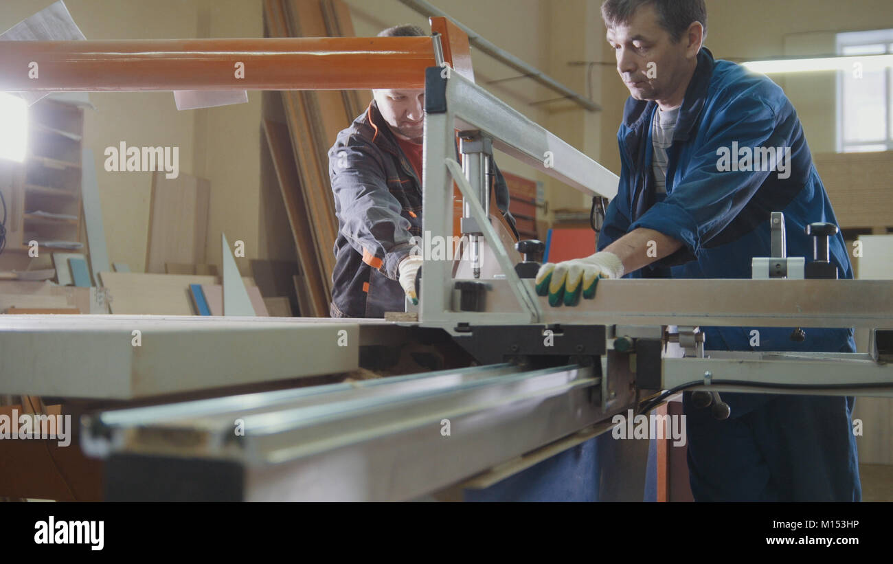 Workers at factory are cutting wooden fragment on electric saw at furniture industry - Stock Image