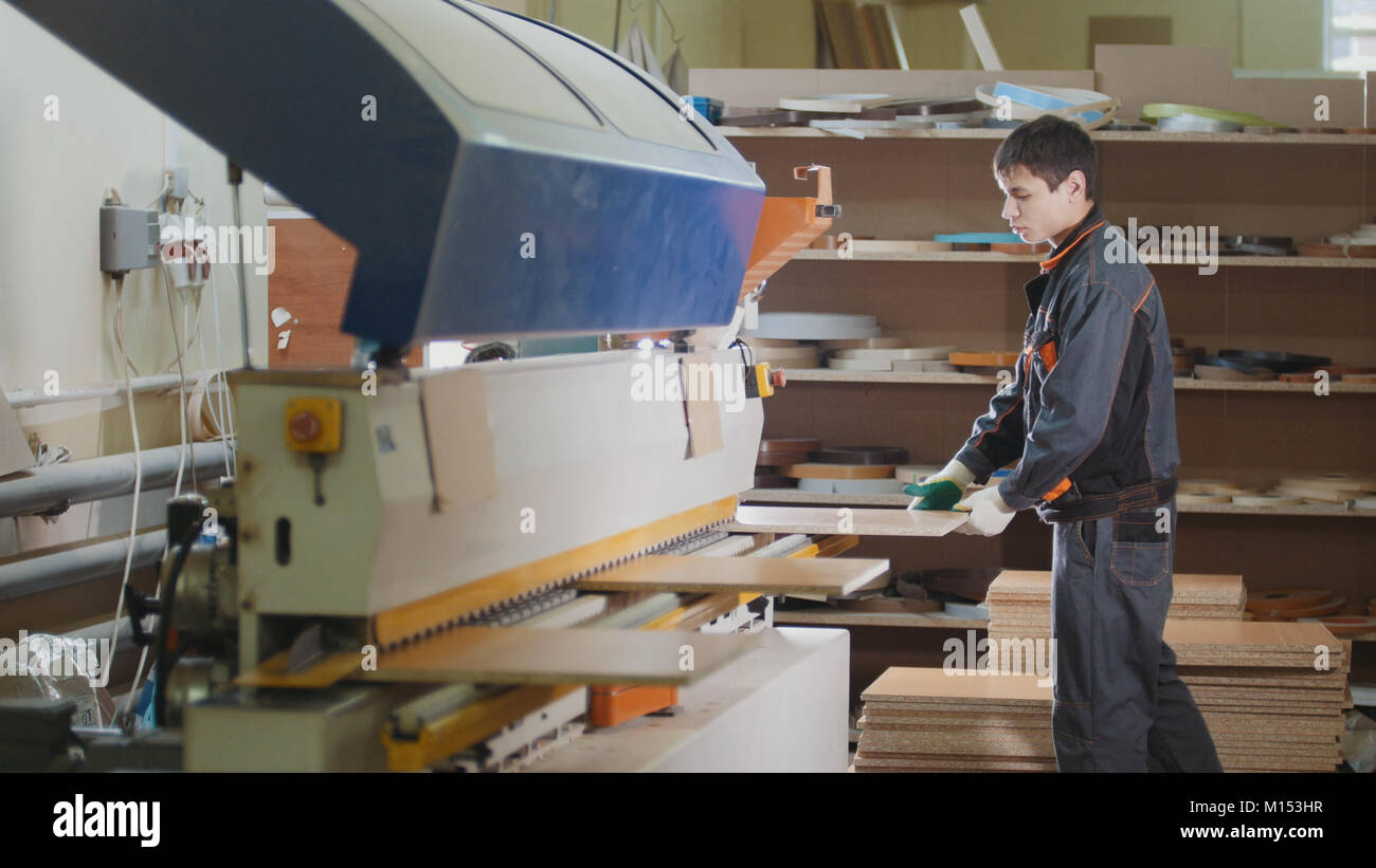 Worker carpenter handles wooden furniture parts on the machine on the factory - Stock Image