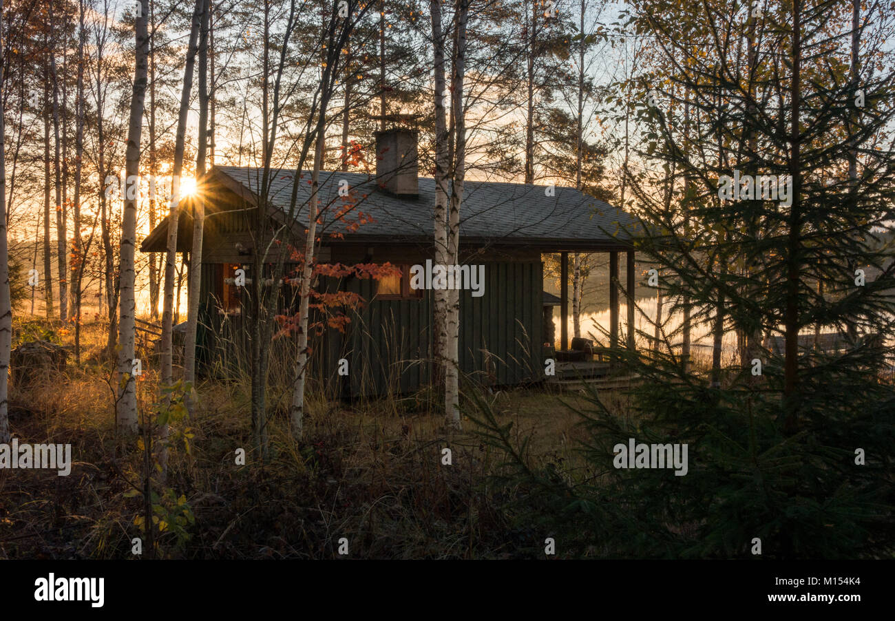 Finnish landscape: traditional lakeside log cabin sauna hidden in a secluded spot on the edge of autumn/winter through - Stock Image