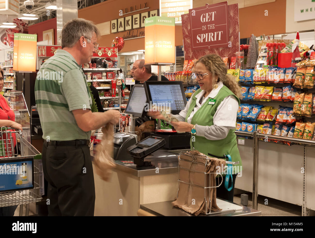 Supermarket cashier counting/handing change to a customer. - Stock Image