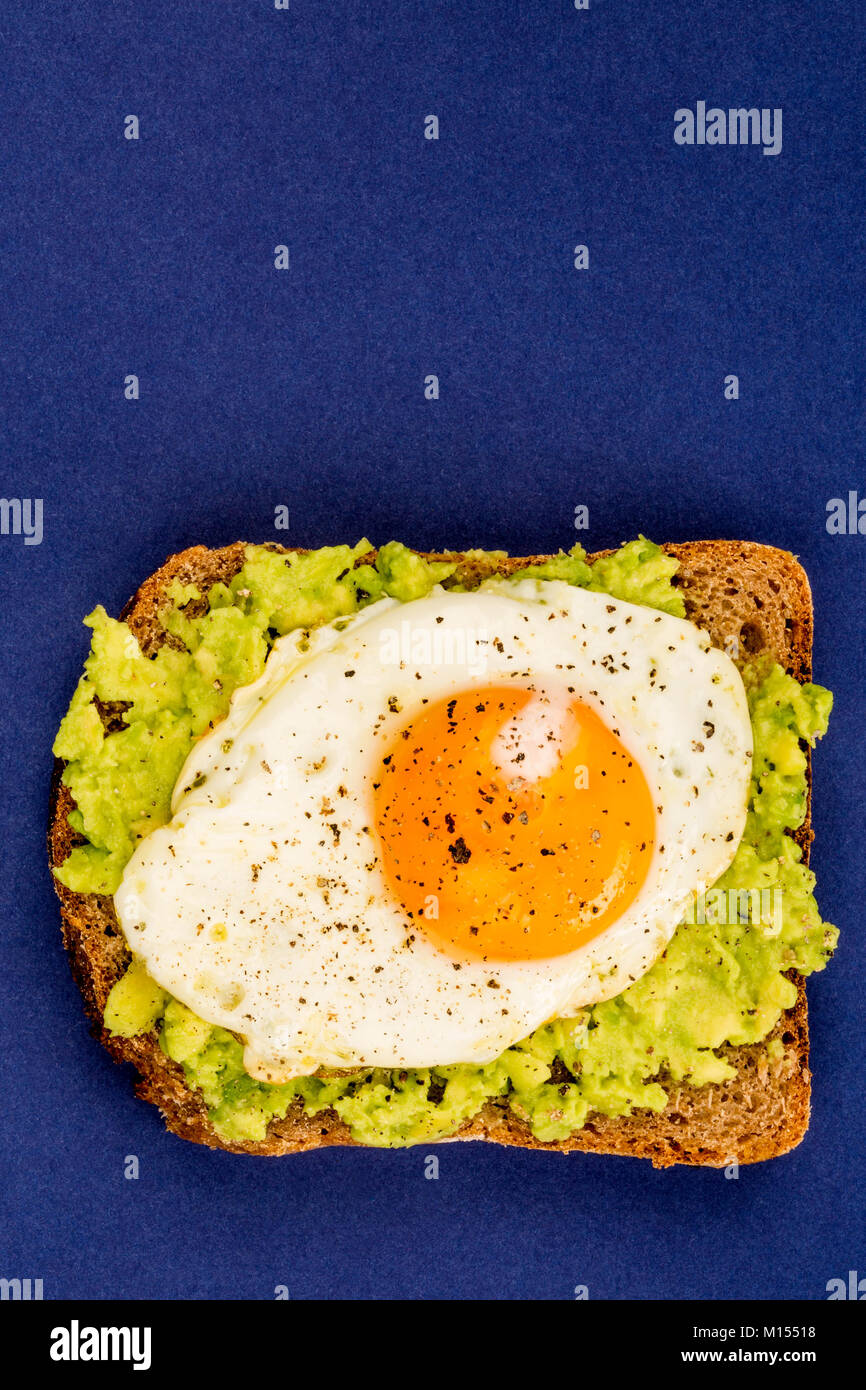 Fried Egg Sunny Side Up on Crushed Avocado And Rye Bread Open Faced Sandwich Against A Blue Background - Stock Image