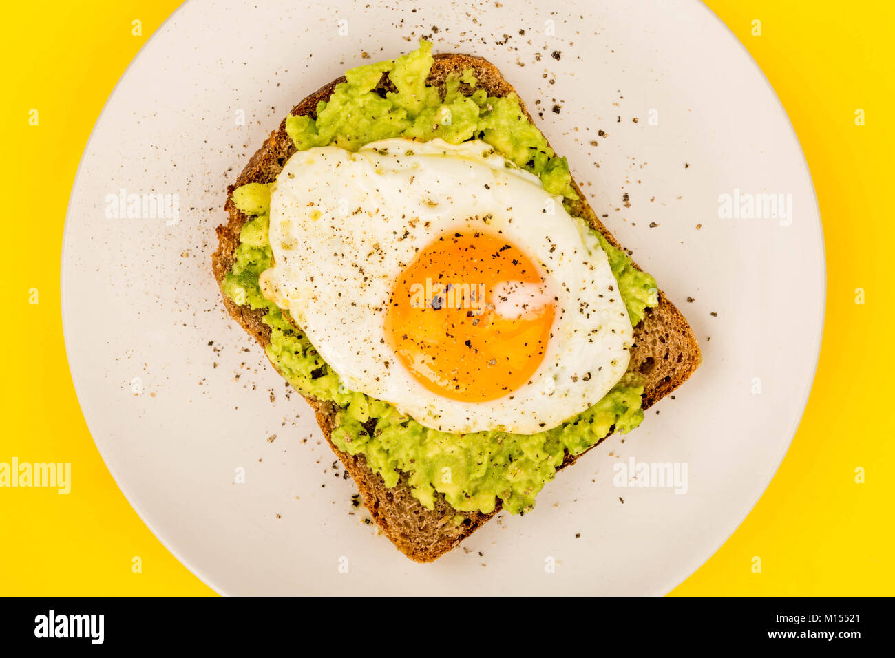 Fried Egg Sunny Side Up on Crushed Avocado And Rye Bread Open Faced Sandwich Against A Yellow Background - Stock Image