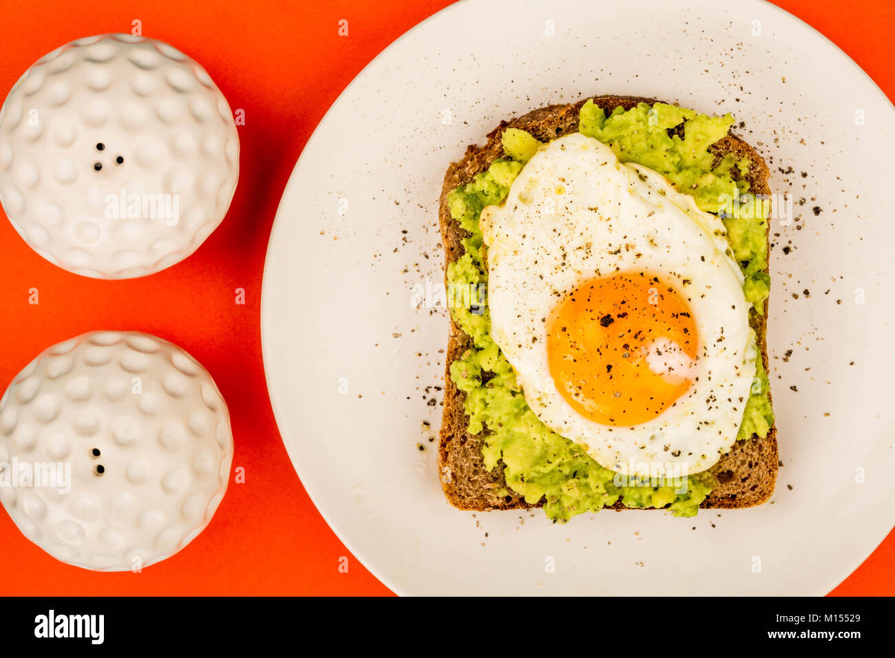 Fried Egg Sunny Side Up on Crushed Avocado And Rye Bread Open Faced Sandwich Against A Red Background - Stock Image