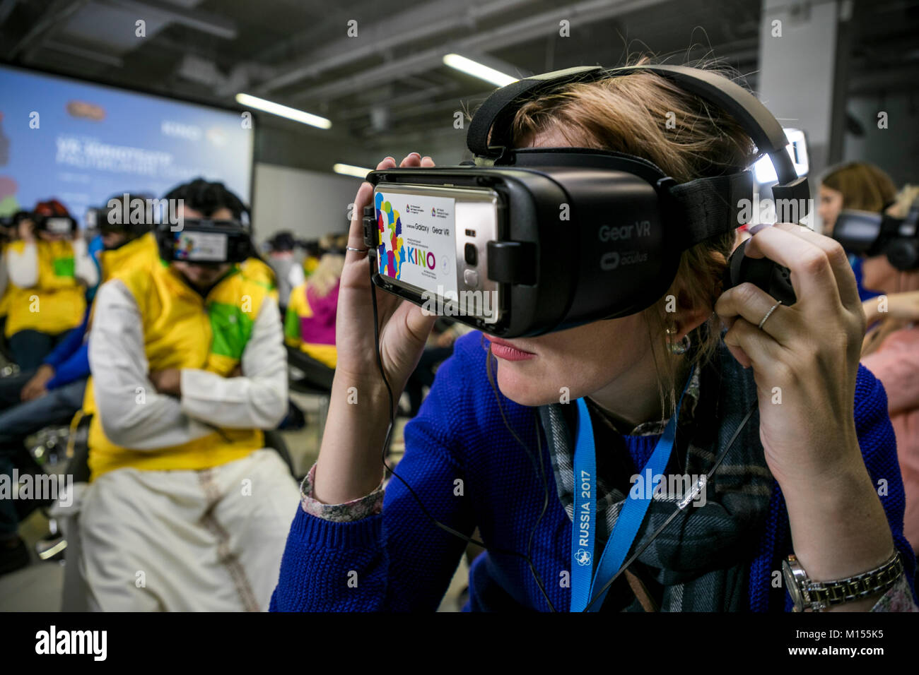 Girl in Samsung Gear VR glasses enthusiastically watching the movie in the virtual reality cinema in Sochi, Russia - Stock Image