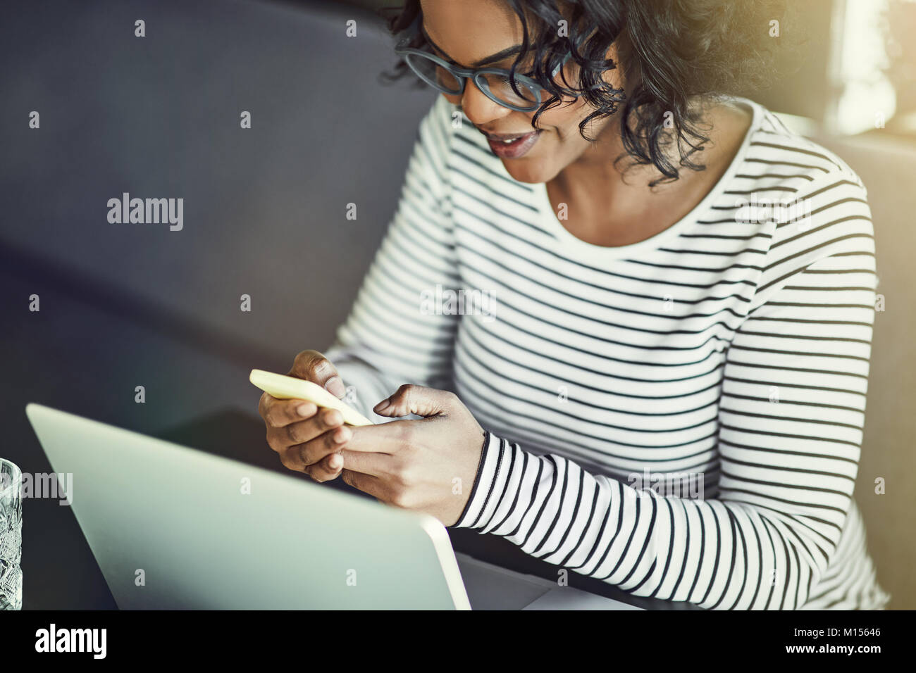 Young African woman wearing glasses sitting alone at a table sending a text message on her cellphone and working - Stock Image