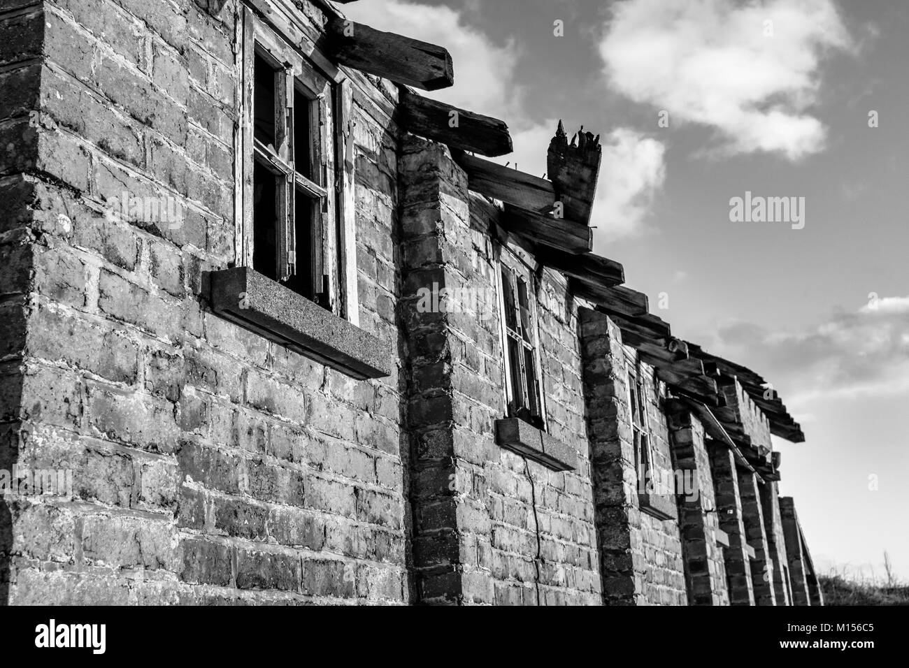 black and white photo of an old brick building with broken windows - Stock Image