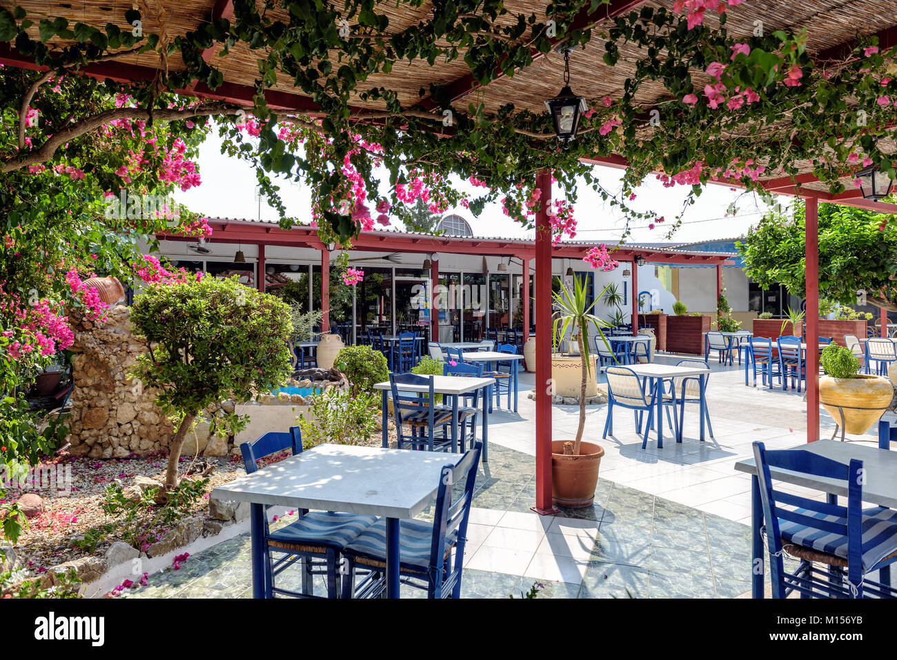 RHODES, GREECE - AUGUST 2017: Traditional Greek tavern with blue tables and chairs on Rhodes island. Stock Photo