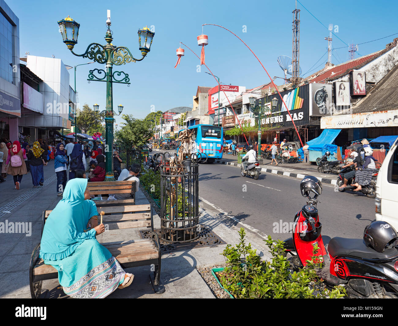 muslim woman sitting on a bench on malioboro street yogyakarta java M159GN