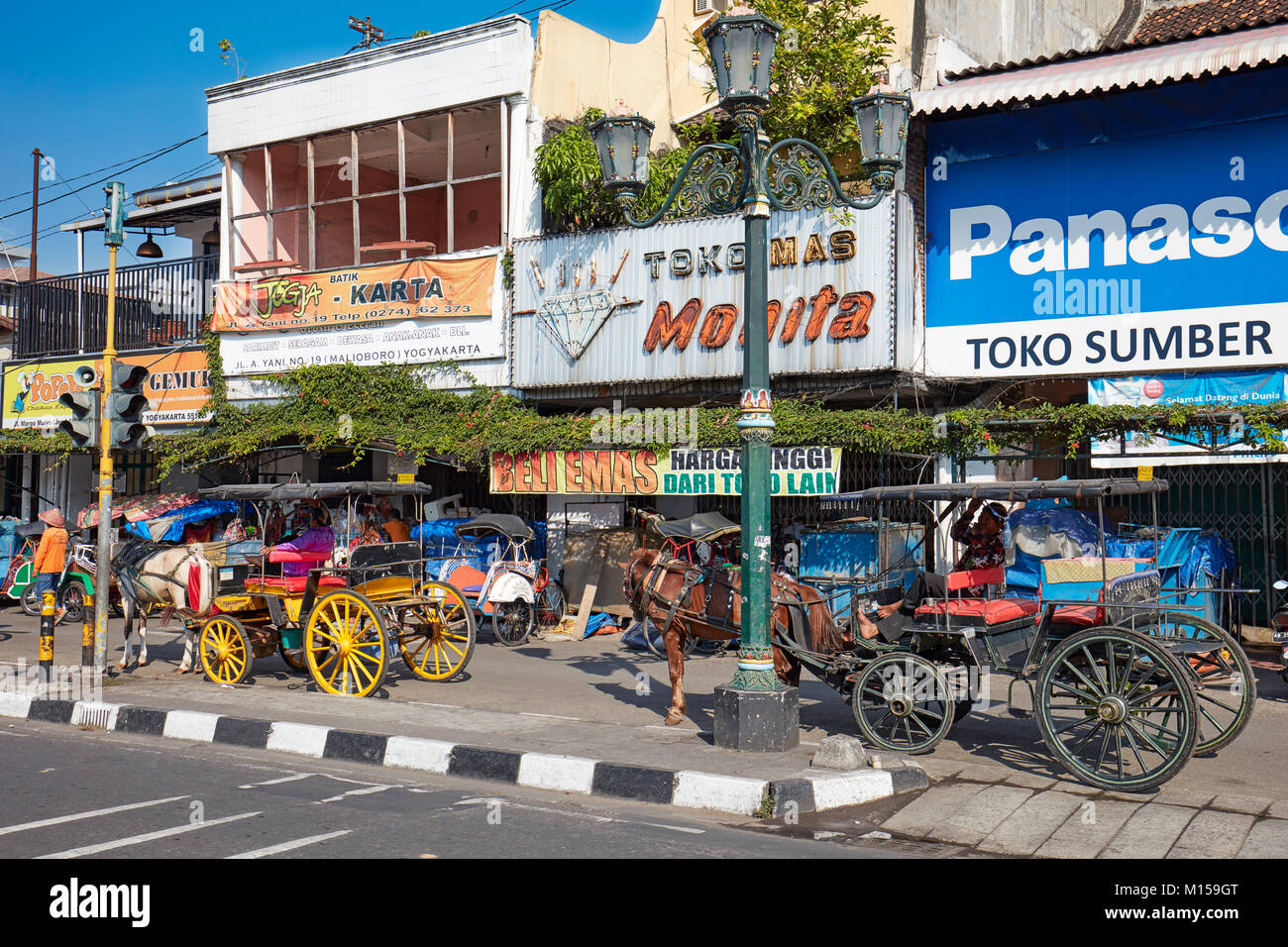 Horse-drawn carriages waiting for customers on Malioboro Street. Yogyakarta, Java, Indonesia. - Stock Image