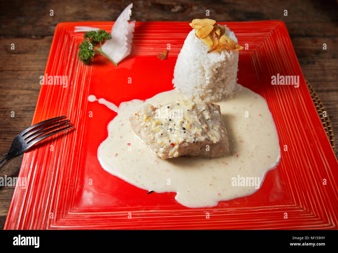 Steamed fillet of mahi-mahi fish in white sauce with rice and garlic chips served in a local warung (small family Stock Photo