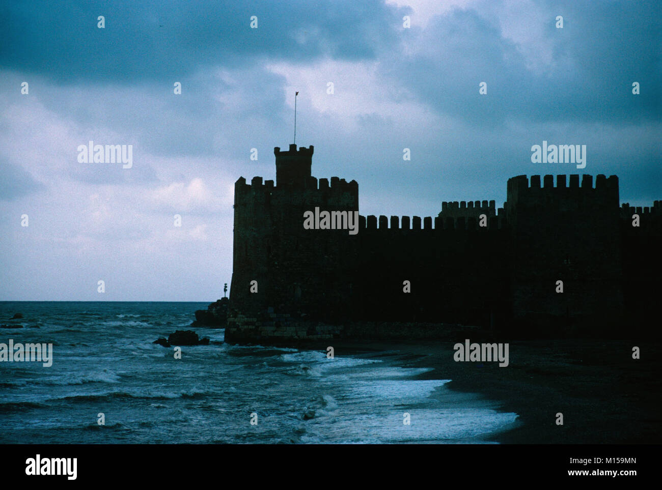 The Dark Outline of Mamure Castle (1221) and Storm Clouds near Anamur on the Mediterranean Coast, Turkey - Stock Image