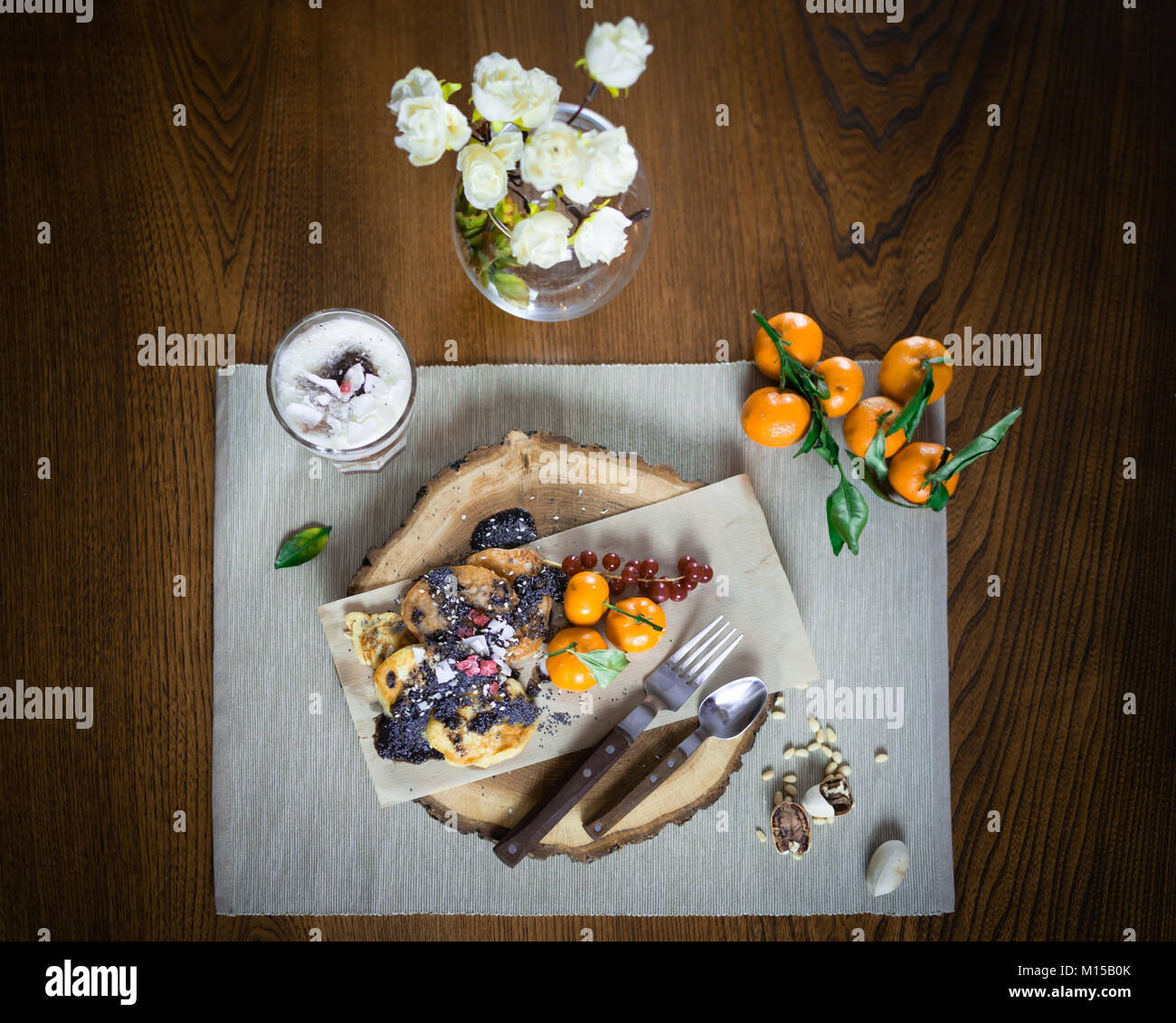 Beautiful dish for breakfast on the stylish wooden tray. Pancakes and parfait with fruits decorated with toppings - Stock Image