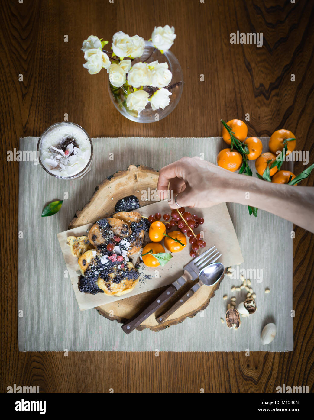 Woman hand decorates dish for breakfast on the wooden tray. Pancakes and parfait decorated with fruits and toppings. - Stock Image
