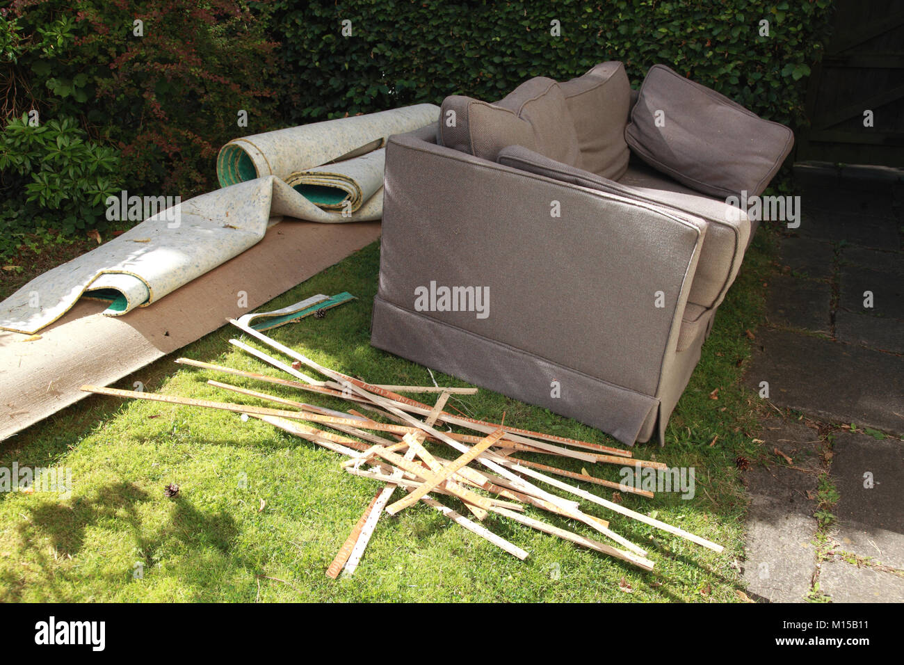 A sofa and a carpet being thrown out because of an infestation of moths - Stock Image