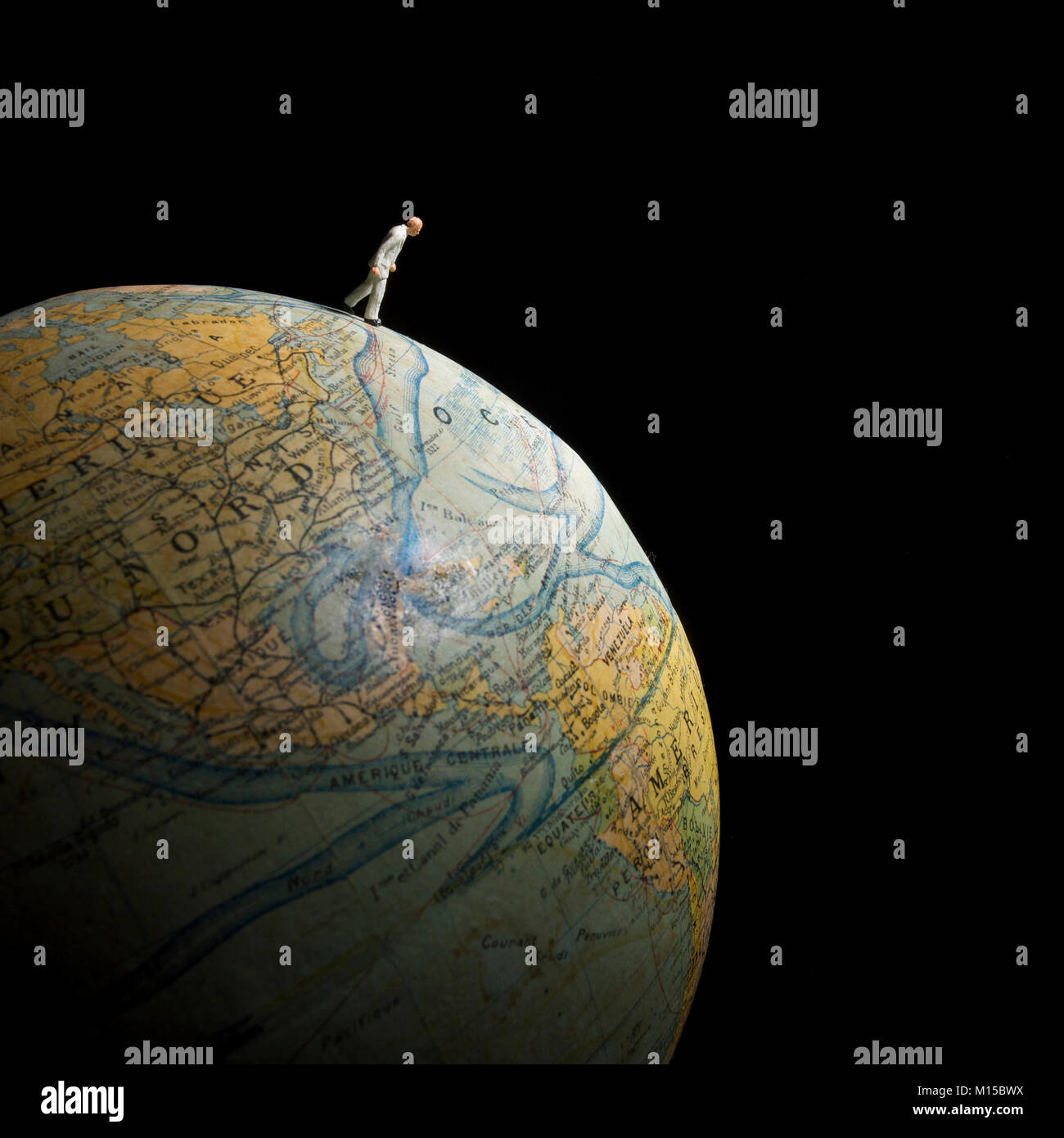 Figurine walking on globe, concept earth - Stock Image