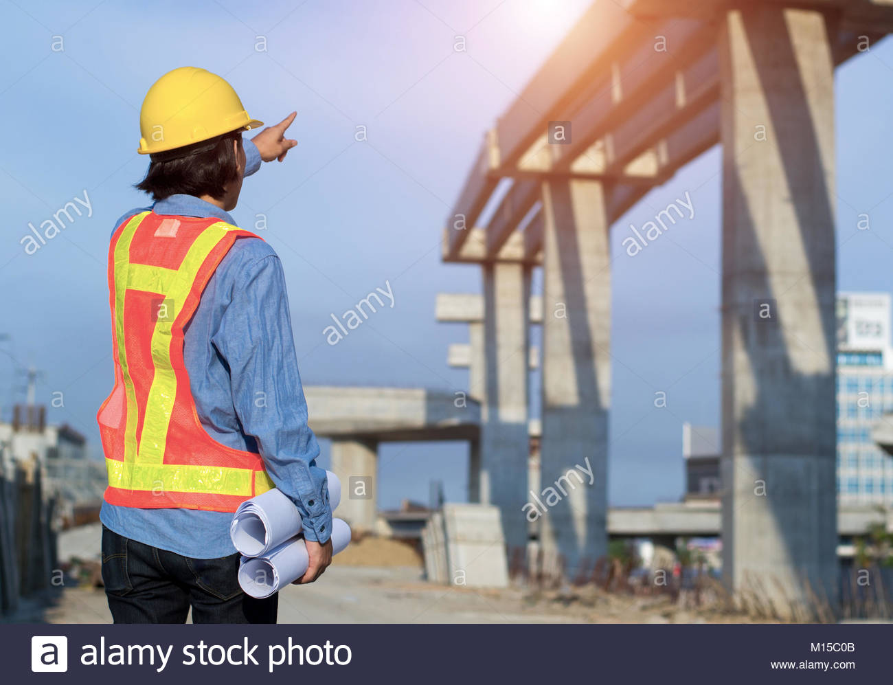 Construction engineer holding construction drawing with foreman worker checking construction site for new Infrastructure - Stock Image