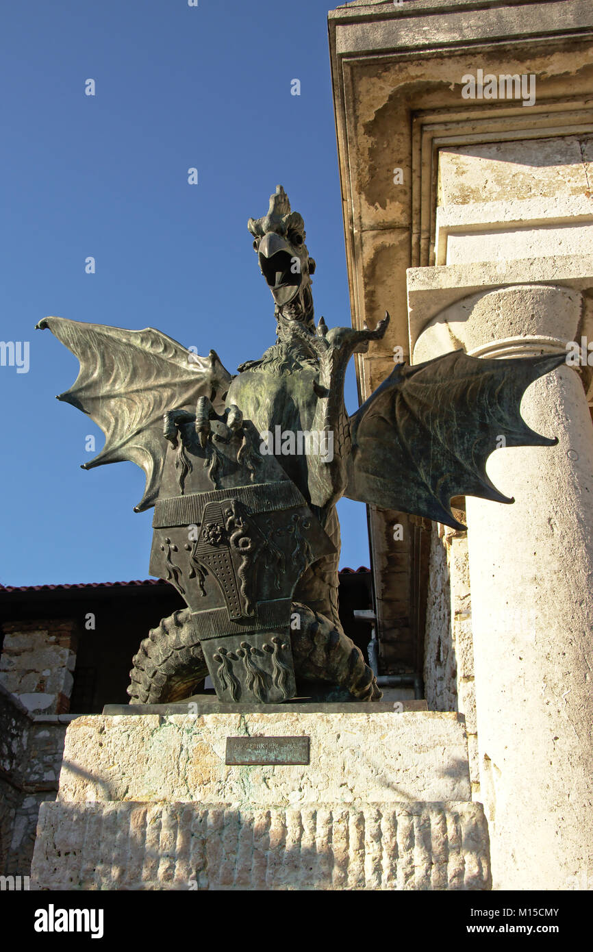 Bronze sculpture of a mythical Basilisk monster with wide open wings and beak,holding a shieeld, found in the courtyard - Stock Image